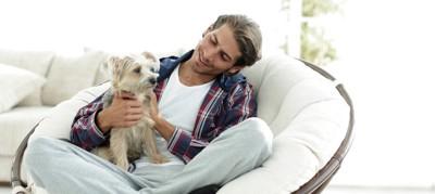 愛犬を膝の上に乗せる男性