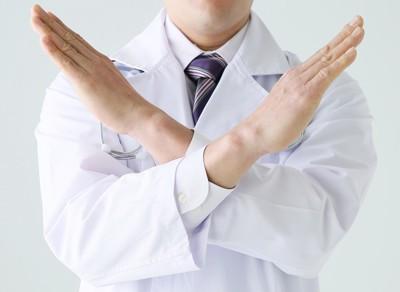 バツのポーズをする医者