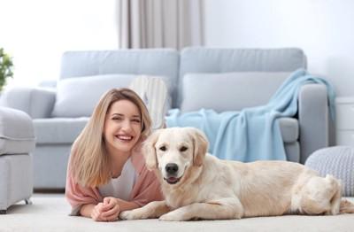床に寝そべる犬と女性