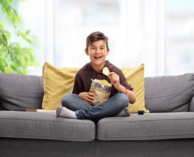ソファーでポテトチップスを食べる少年