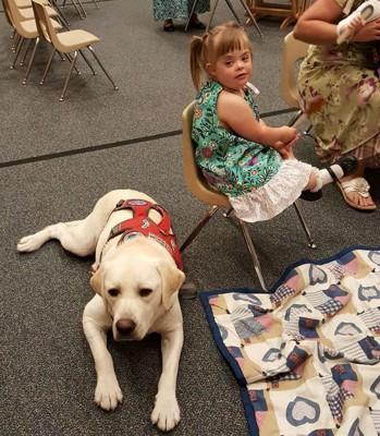 椅子の座る少女と犬