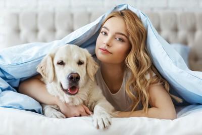 ベッドでくつろぐ飼い主と犬