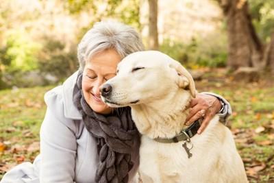 シニア女性に寄り添って目を閉じる犬