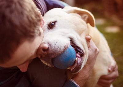 青いボールを咥えて飼い主さんと遊ぶ犬