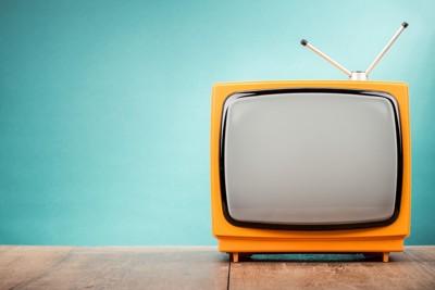 水色の壁面に置かれたレトロなオレンジのテレビ