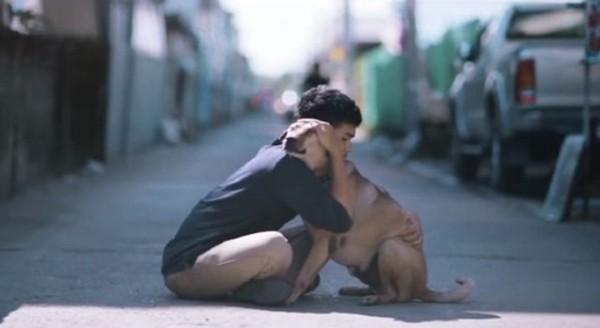 茶色い犬を抱く男性