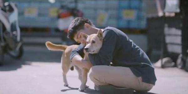 立っている犬を抱く男性