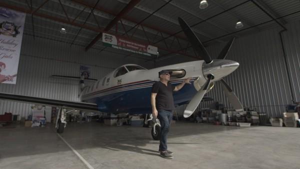 飛行機の横に立つ男性